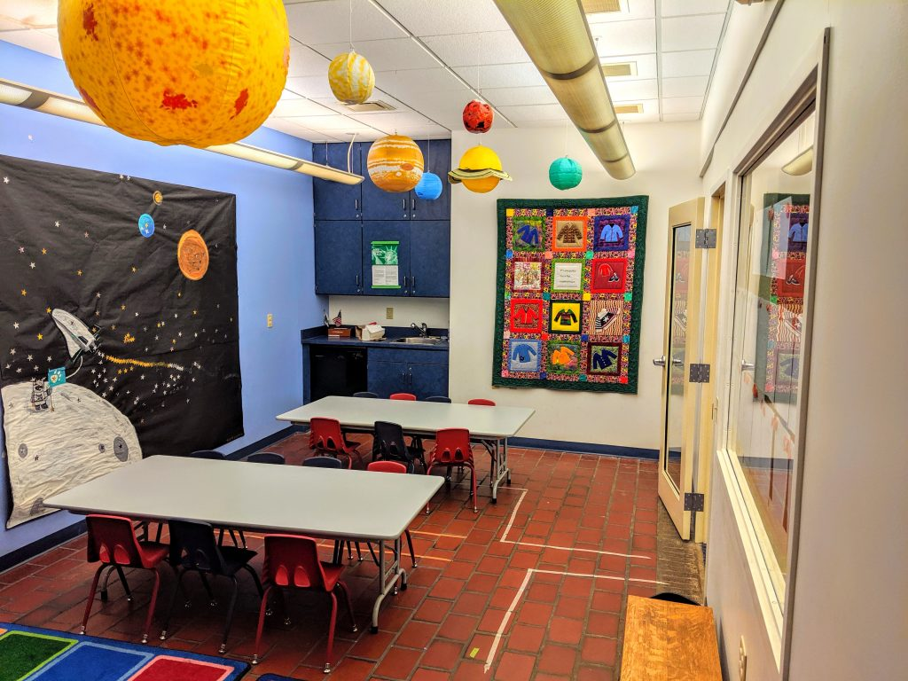 The children's programming room at C.C. Mellor Library- Edgewood. The room contains 2 child-sized tables with chairs. The room has a space-themed poster on the wall and large inflatable planets hanging from the ceiling. There is a colorful rug to one side, and a quilt showing Mr. Rogers' sweaters hanging on the wall.