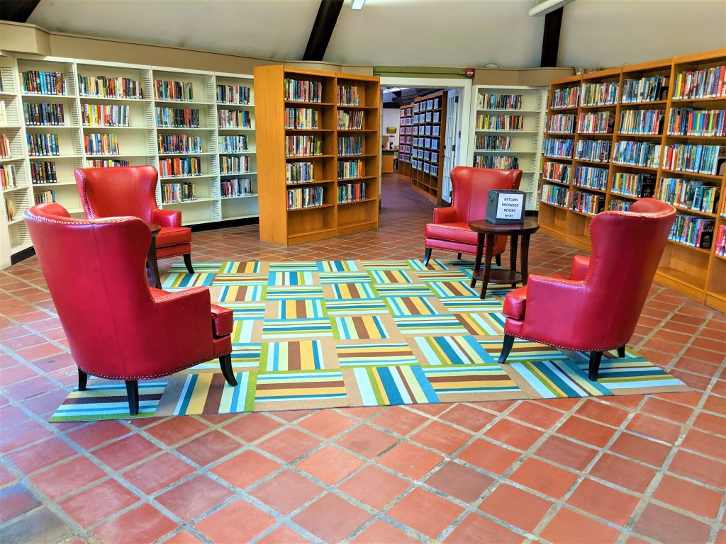 The fiction room at C.C. Mellor Library- Edgewood. The room is lined with bookshelves. In the middle of the room are 4 large red armchairs on a colorful rug.