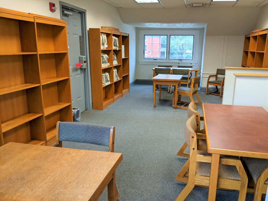 The quiet study room at C.C. Mellor Library- Edgewood. The room is lined with several wooden bookshelves. There are 2 large tables and 2 small desks with chairs.